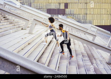 interracial sporty couple training running up stairs in the city. fitness, urban sports workout and healthy lifestyle concept, copy space for text - Stock Photo