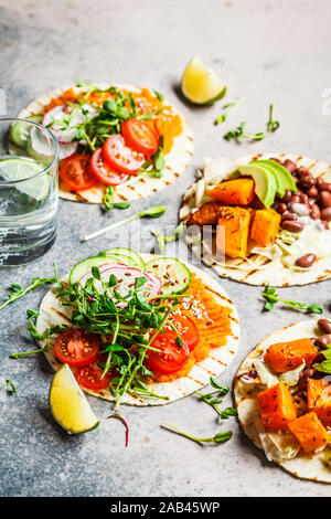 Open vegan tortilla wraps with sweet potato, beans, avocado, tomatoes, pumpkin and seedlings on a gray background, flat lay. Healthy vegan food concep - Stock Photo