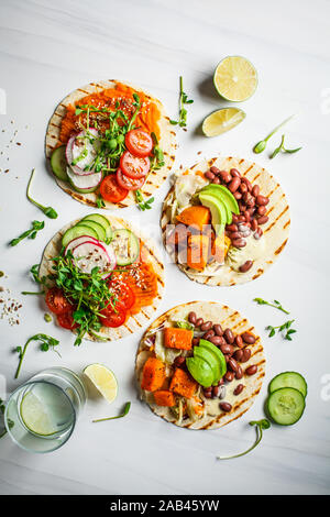 Open vegan tortilla wraps with sweet potato, beans, avocado, tomatoes, pumpkin and seedlings on a white background, top view, flat lay. Healthy vegan - Stock Photo