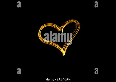 Long exposure photograph of neon gold color in a heart outline shape, against a black background. Light painting photography. Love, romance concept - Stock Photo