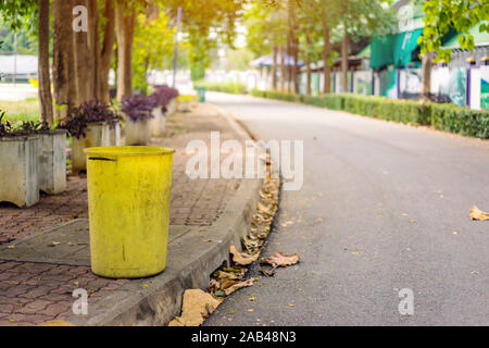 An old yellow dustbin in the public park beside the walk way for protect environment. - Stock Photo