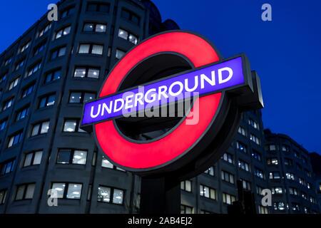 LONDON - NOVEMBER 20, 2019: London Underground tube red logo sign train station at night - Stock Photo