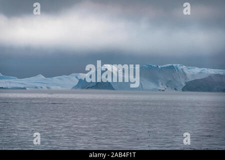 Stranded icebergs in the fog at the mouth of the Icefjord near Ilulissat. Nature and landscapes of Greenland. Travel on the vessel among ices - Stock Photo