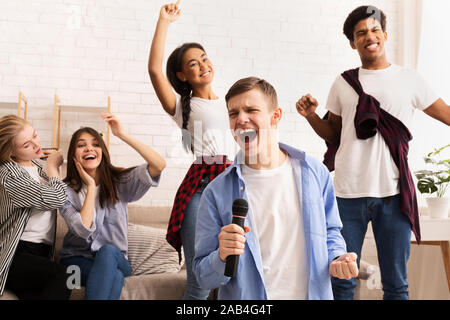 Friendship and home entertainment. Teens singing karaoke - Stock Photo