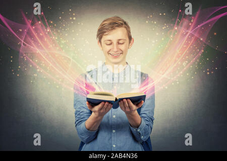 Overjoyed boy teenager smiling as holding a opened bewitched textbook. Magic book concept, different lights and glows telling an interesting and engag - Stock Photo
