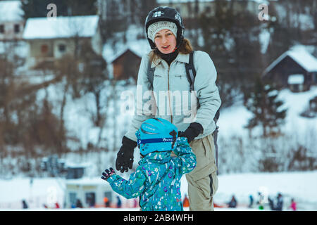 LVIV, UKRAINE - January 12, 2019: mother teaching little girl to snowboarding - Stock Photo
