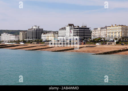 Seafront hotels and multiple groynes on Eastbourne beach, viewed here on an overcast day in May 2019. - Stock Photo
