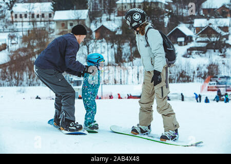 LVIV, UKRAINE - January 12, 2019: young family. father with mother teaching little girl how to snowboarding - Stock Photo