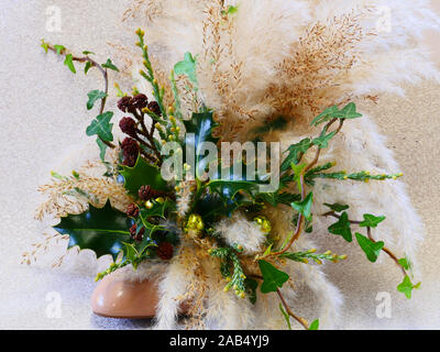 Christmas arrangement holly, ivy and pampas grass in a shoe front view - Stock Photo