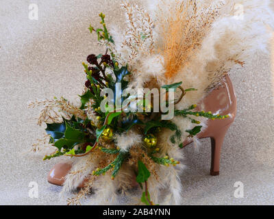 Christmas arrangement holly, ivy and pampas grass in a shoe, side view - Stock Photo