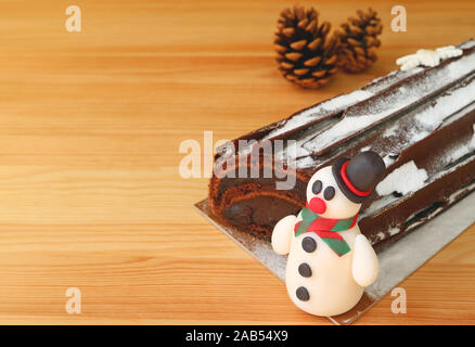 Closeup a Cute Snowman Marzipan of Christmas Roll Cake on Wooden Table with Blurry Dry Pine Cones in Background - Stock Photo