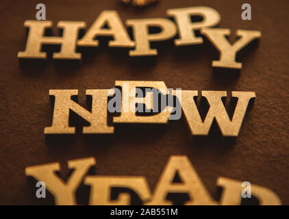 Happy New Year wallpaper made with rustic wooden letters edited with vintage film filter.Winter holiday background with hand made letters - Stock Photo
