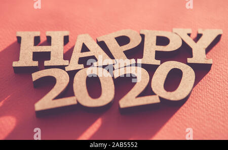 Happy 2020 background.Red wallpaper with wooden rustic style letters shot on paper backdrop,edited with fading film filter and low contrast.Winter hol - Stock Photo