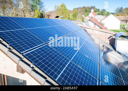 Solar panels and sunlight reflextions on the roof against blue sky background. Concept clean power energy.