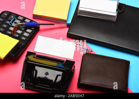 Office tools isolated on pink and blue background, close up. Mans leather wallet and stationery. Calculator, hole punch, notebook, card holder, note paper, pen and clips. Business and work concept.