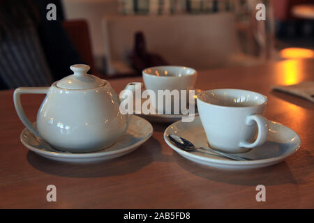 Tea set for two. Сeramic teapot and cups (bowls) with fragrant hot tea on blurry background. New Year's festive table in a small café - Stock Photo