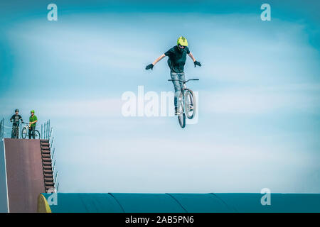 Young unrecognizable Bmx rider making a bike jump on a high springboard. Extreme sport - Stock Photo