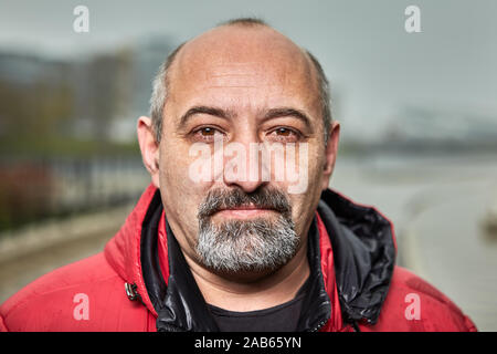 Bald mature bearded man in red jacket is standing outdoors. Portrait of the aged male in warm clothes on the street in the fall.
