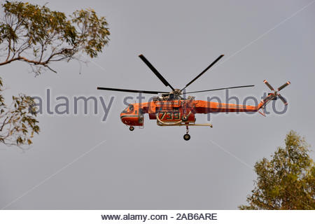 An Erickson air-crane - nicknamed 'Jerry' - flys low over Woombah; taking water from the Clarence River, and quelling the flames of threatening fires. - Stock Photo