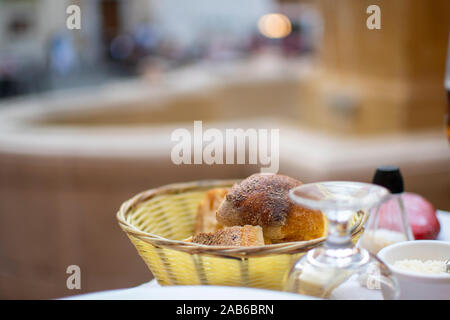 A basket of bread and rolls on a patio table in a piazza in front of a fountain in Nice France. - Stock Photo