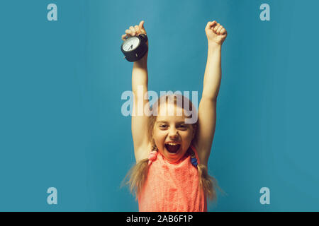 Pupil with braids, isolated on blue background. Back to school and childhood concept. Girl with black alarm clock. Kid screams with happy face and hands up. - Stock Photo