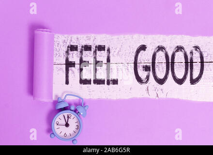 Word writing text Feel Good. Business photo showcasing relating to or promoting an often specious sense of satisfaction Alarm clock and torn cardboard - Stock Photo