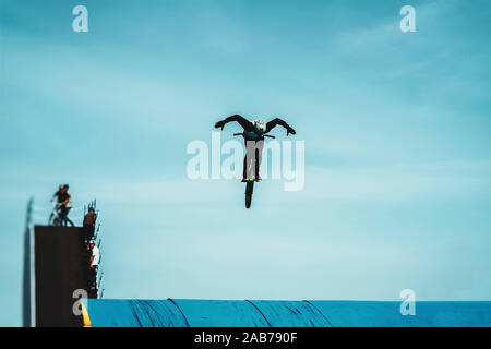 Silhouette of a unrecognizable young bike rider performing aerial BMX trick against blue sky. Extreme sport, youth culture