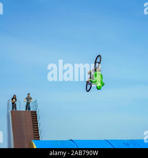 Aerial BMX stunt. Young unrecognizable bike rider performing air trick back flip. Extreme sport, youth culture and leisure - Stock Photo