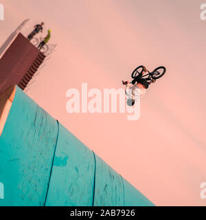 Young unrecognizable Bmx rider performing air trick back flip. Extreme sport. Intentional angle to the horizon - Stock Photo