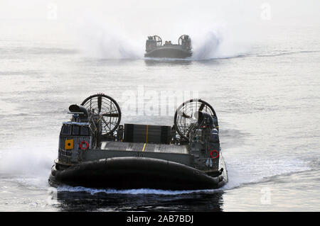 SAN DIEGO (Aug. 30, 2012) Landing Craft Air Cushion (LCAC) 24 and 73, from Assault Craft Unit (ACU) 5, approach the well deck of the amphibious assault ship USS Boxer (LHD 4).  Boxer is currently underway off the coast of Southern Calif. - Stock Photo