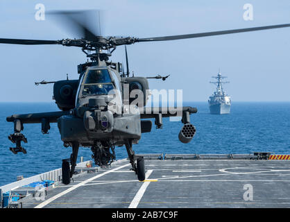 (Nov. 11, 2012) A U.S. Army AH-64D Apache helicopter takes off from Afloat Forward Staging Base (Interim) USS Ponce (AFSB(I) 15), during an exercise as the guided-missile destroyer USS Benfold (DDG 65) transits nearby. Ponce, formerly designated as an amphibious transport dock ship, was converted and reclassified to fulfill a long-standing U.S. Central Command request for an AFSB to be located in the U.S. 5th Fleet area of responsibility. Stock Photo