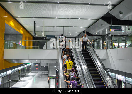 Asia / Singapore - Nov 23, 2019 : Unidentified Asian people on stairs escalator in a subway station. - Stock Photo
