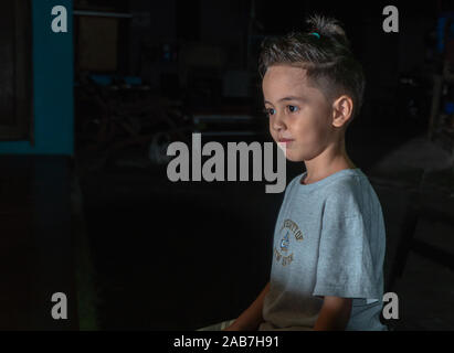 A cute boy with a spiky hairstyle sitting in the dark - Stock Photo