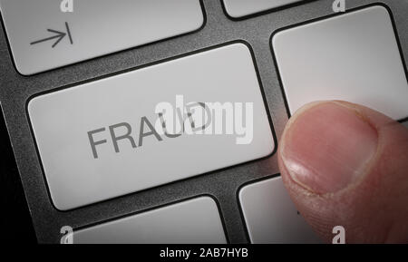 A man pressing a key on a computer keyboard with the word fraud, online fraud concept image