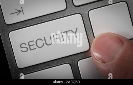 A man pressing a key on a computer keyboard with the word security. Internet security concept image.
