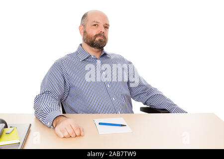 Ein Mann mit Bart an seinem Schreibtisch vor weissem Grund - Stock Photo