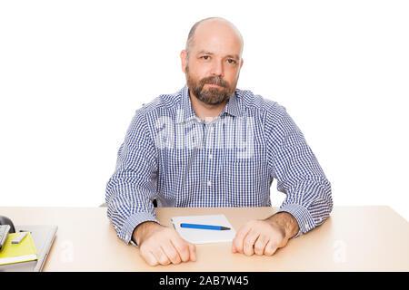 Ein Mann mit Bart an seinem Schreibtisch mit Notizblock und Kugelschreiber vor weissem Grund - Stock Photo