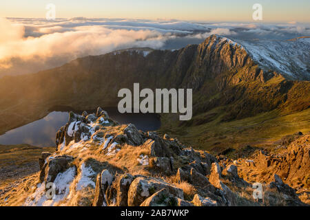 Morning light illuminates the top of Craig Cau during a cloud inversion, photographed from the top of Cadair Idris, Snowdonia, Wales, United Kingdom - Stock Photo