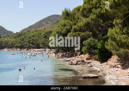 People relaxing in the calm waters of the beautiful bay of Playa (Platja) de Formentor on the northern coast of Mallorca, Balearic Islands, Spain - Stock Photo