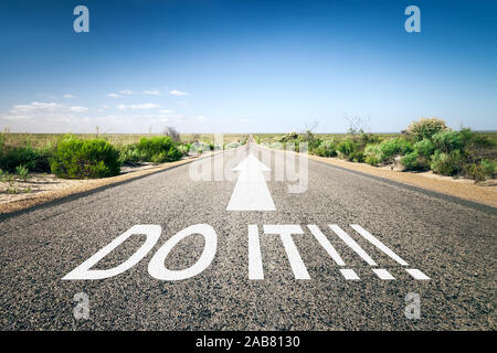 Eine unendlich lange Strasse mit der wegweisenden Aufschrift: 'Do It!' - Stock Photo