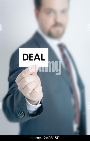 Ein Geschaeftsmann, der eine Visitenkarte mit den Worten 'Deal' in der Hand haelt - Stock Photo