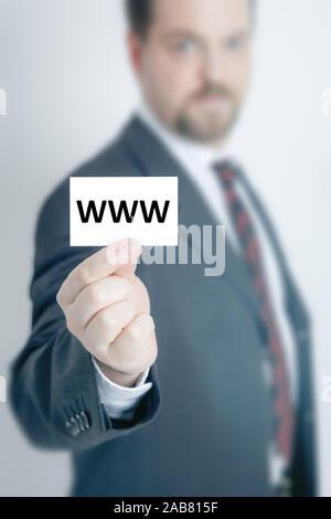 Ein Geschaeftsmann, der eine Visitenkarte mit den Buchstaben 'www' in der Hand haelt - Stock Photo
