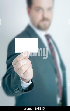 Ein Geschaeftsmann, der eine unbeschriebene Visitenkarte in der Hand haelt - Stock Photo