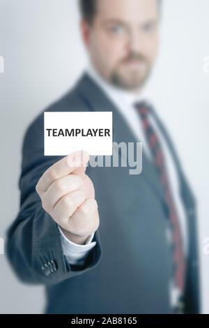 Ein Geschaeftsmann, der eine Visitenkarte mit den Worten 'Teamplayer' in der Hand haelt - Stock Photo