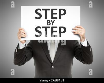 Ein Geschaeftsmann, der ein Schild mit den Worten 'Step by Step' haelt - Stock Photo
