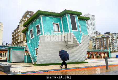 Brighton UK 26th November 2019 - A walker with an umbrella passes by the Upside Down House on Brighton seafront as the remnants of Tropical Storm Sebastien arrive in Britain bringing strong winds and rain to most parts of the country . Credit: Simon Dack / Alamy Live News - Stock Photo