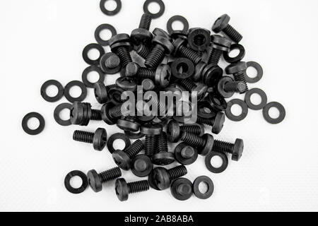 Screws and black washers piled on a white background - Stock Photo