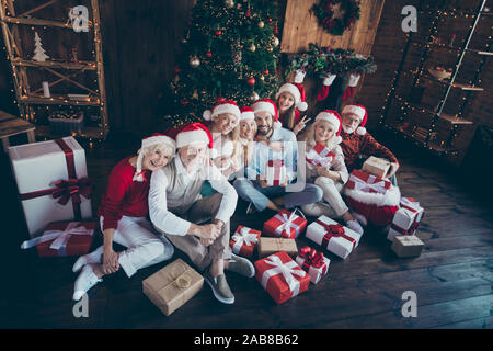Top above high angle view photo of cheerful family with granddaughter showing v-sign surrounded with wrapped boxed sitting on floor under fir tree - Stock Photo