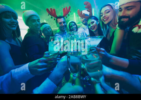 Cropped photo of best friends company holding sparkling wine glasses counting last seconds to newyear excited mood wear dresses shirts pants santa hat - Stock Photo