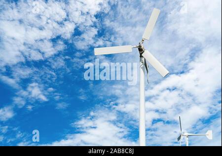 Wind turbine at wind farm on blue sky. Alternative and renewable energy concept. Sustainable electricity. Green energy concept. Small turbine. Clean